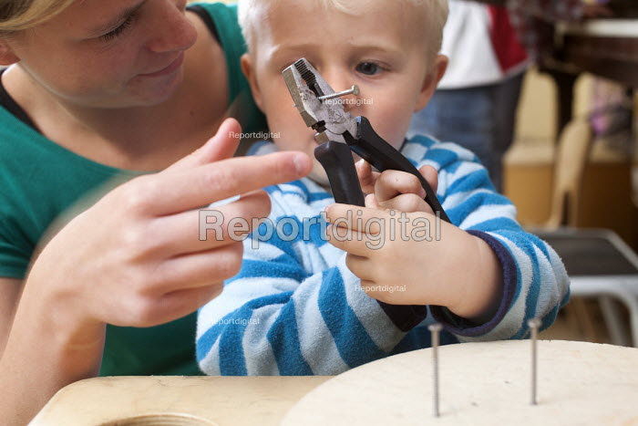 A young boy using pliers and nails with encouragement from a nursery worker. Norland Nursery, Bath. - Paul Box - 2012-06-27