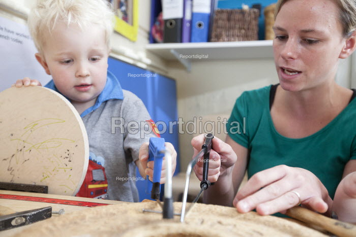 A boy using a hacksaw with encouragement from a nursery worker. Norland Nursery, Bath. - Paul Box - 2012-06-27