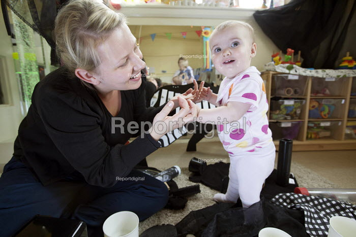 A baby girl playing and a nursery worker, Norland Nursery, Bath. - Paul Box - 2012-06-27