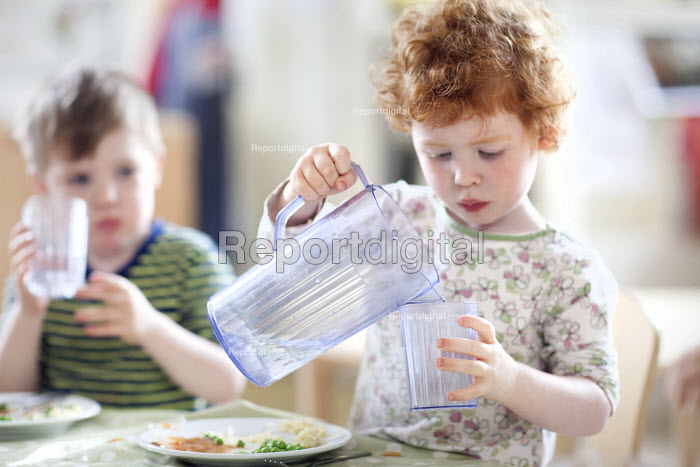 A young girl pouring into a glass from a jug of water, Norland Nursery, Bath. - Paul Box - 2012-06-27