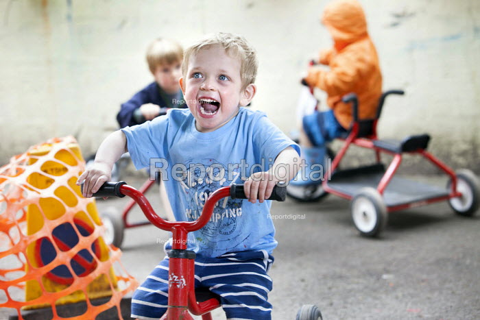 Children playing on tricycles outside, Norland Nursery, Bath. - Paul Box - 2012-06-27