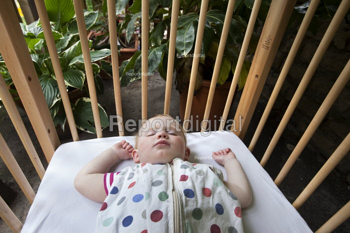 A baby sleeping in a cot outside, Norland Nursery, Bath. - Paul Box - 2012-06-27