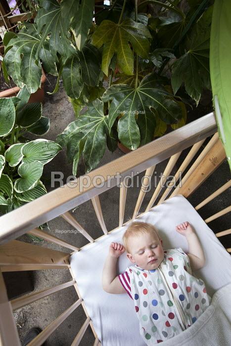 A baby sleeping in a cot outside, Norland Nursery, Bath. - Paul Box - 2012-06-27