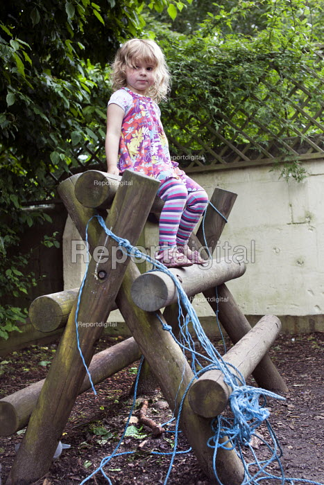 A girl playing outside on a climbing frame, Norland Nursery, Bath. - Paul Box - 2012-06-27