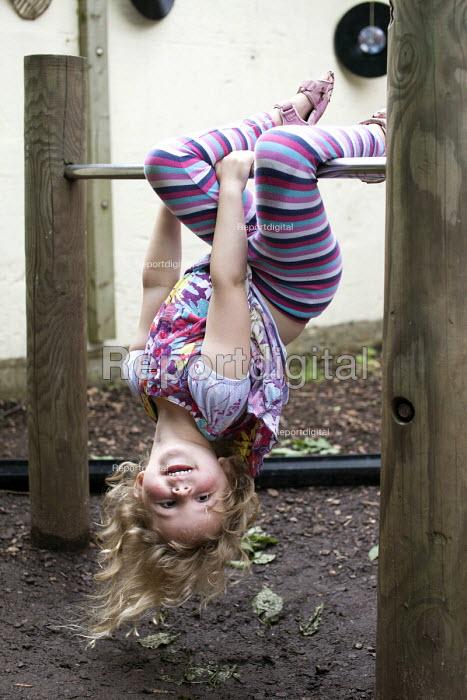 A girl playing outside on a climbing frame, Norland Nursery, Bath. - Paul Box - 2012-06-27