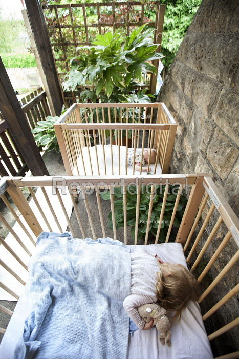 A girl sleeping in a cot outside, Norland Nursery, Bath. - Paul Box - 2012-06-27