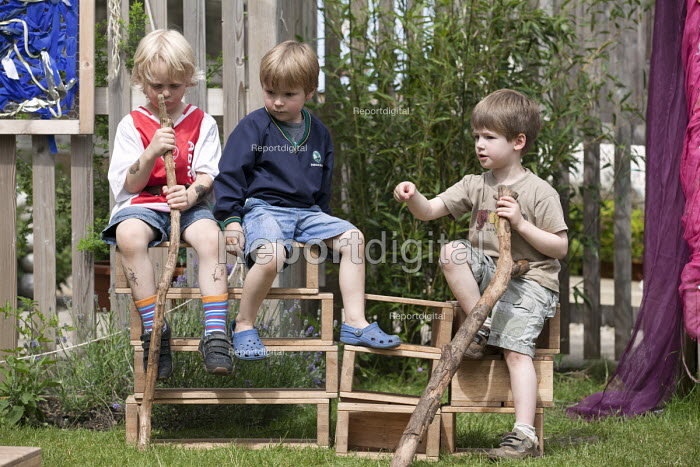 Boys playing outside on wooden boxes in discussion, Norland Nursery, Bath. - Paul Box - 2012-06-27
