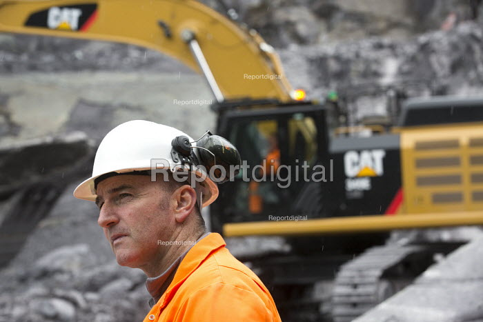 A quarry worker in front of a digger at Welsh Slate, Penrhyn quarry, Bethesda, North Wales. - Paul Box - 2013-08-12