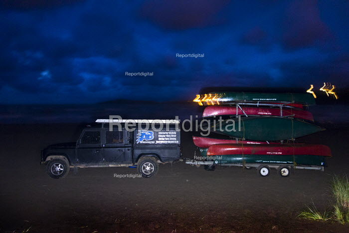 An outdoor activities company loads its canoes onto a trailer at Poppit sands, Cardigan, Pembrokeshire, Wales. - Paul Box - 2013-09-07