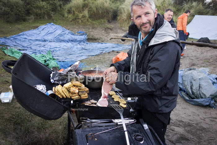 An outdoor activities organiser cooking on a barbecue for a stag party who are staying overnight in the dunes at Poppit sands, Cardigan, Pembrokeshire, Wales. - Paul Box - 2013-09-08