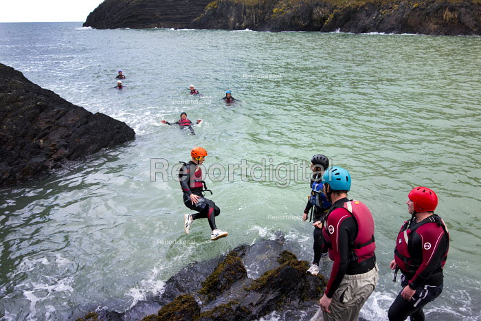 A stag party coasteering, exploring a rocky coastline, Moylegrove, Cardigan, Pembrokeshire, Wales. - Paul Box - 2013-09-08