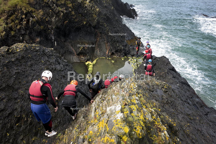A stag party coasteering, exploring a rocky coastline, Moylegrove, Cardigan, Pembrokeshire, Wales. - Paul Box - 2013-09-08