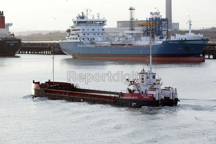A Sludge Carrier passes an oil tanker berthed at a terminal, Fawley Refinery, Oil refinery, Southampton Water. - Paul Box - 2015-01-07