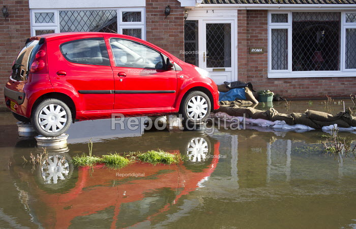 A new car is parked on alloy wheels in an attempt to keep it from the rising flood waters in Moorland on the Somerset levels. - Paul Box - 2014-02-07