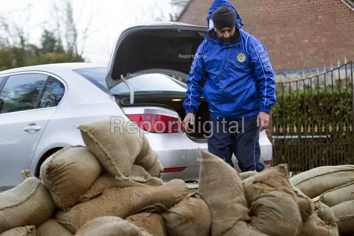 A resident loads his BMW boot with sandbags, Wraysbury, Berkshire after the Thames burst its banks. - Paul Box - 2014-02-12