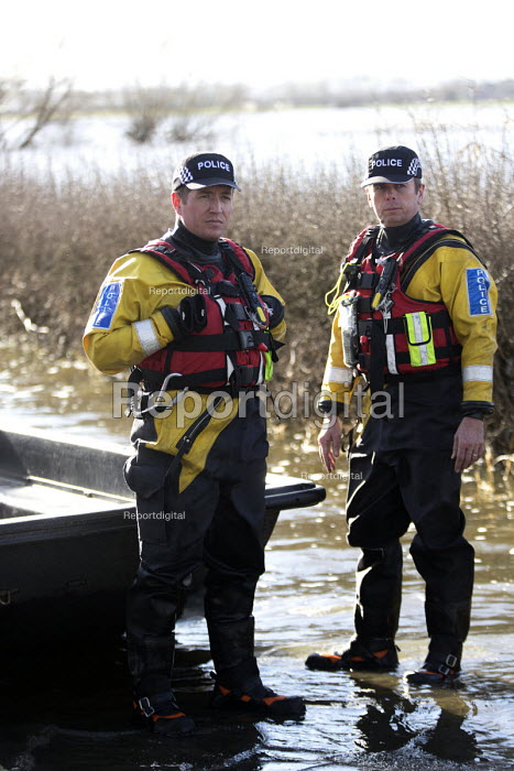 Police escort residents via boat to their homes in Moorland, Somerset after the river Parrett breaks its banks. - Paul Box - 2014-02-04