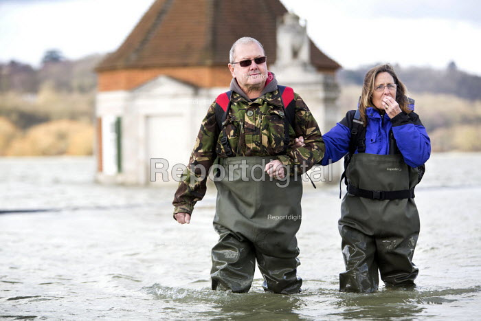Residents of Windsor, Berkshire which has been flooded after the Thames burst its banks wade through flood waters. - Paul Box - 2014-02-13