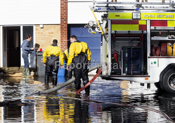 A resident brings tea and biscuits to firefighters to have a break. Firefighters pump water from flooded properties in Datchet , Berkshire which has been flooded after the Thames burst its banks. - Paul Box - 2014-02-13