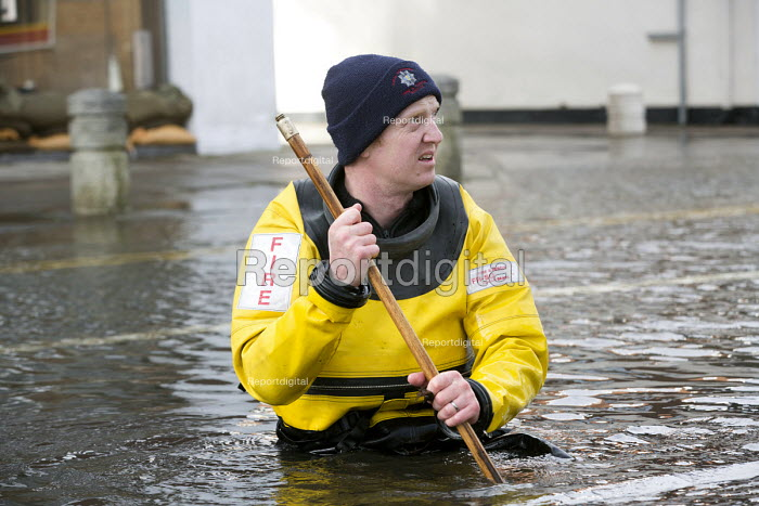 A blocked drain is cleared by a Firefighter as they pump water from flooded properties in Datchet , Berkshire which has been flooded after the Thames burst its banks. - Paul Box - 2014-02-13