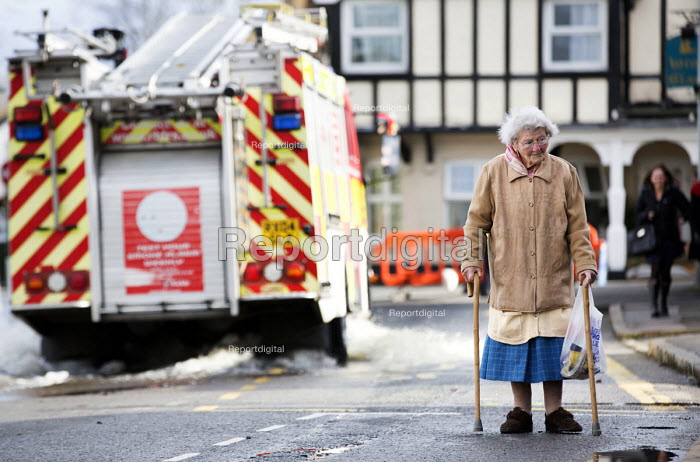 An Elderly lady on crutches in Datchet , Berkshire which has been flooded after the Thames burst its banks. - Paul Box - 2014-02-13