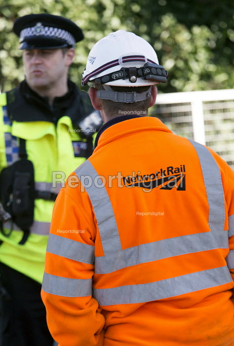 Network rail workers talk with police as they clean up after the railway line flooded in Datchet , Berkshire which has been flooded after the Thames burst its banks. - Paul Box - 2014-02-13