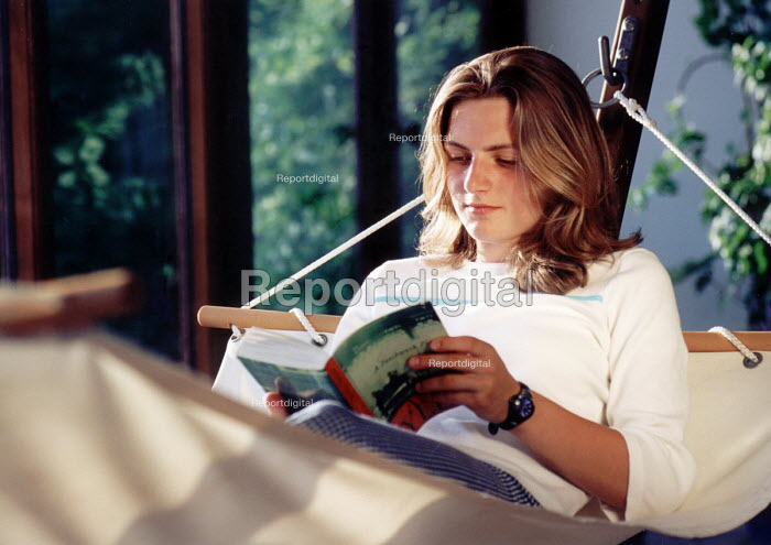 Young woman relaxes on hammock reading a book - Paul Box - 2001-06-25