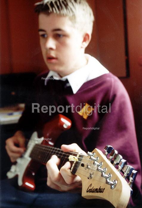 Pupil of Hanham High School, Bristol playing guitar in music lesson - Paul Box - 2001-06-15