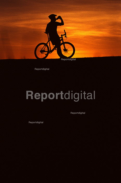 Mountain bike cyclist stops for a drink. - Paul Box - 2002-07-14