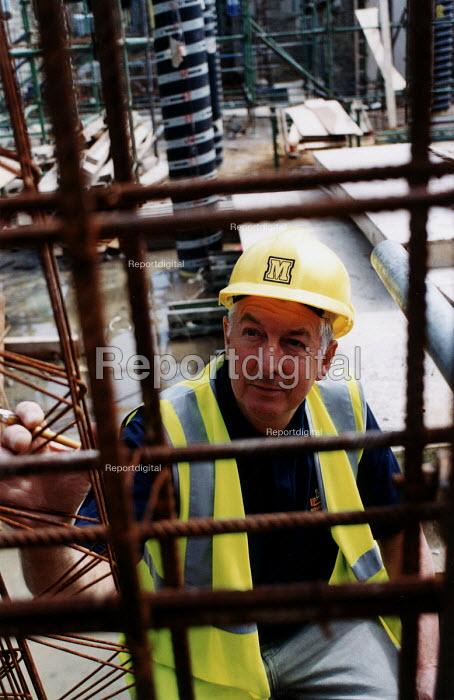 Construction worker checking metal mesh. Midas construction site restoration of Whatley Manor, Malmesbury - Paul Box - 2002-10-14
