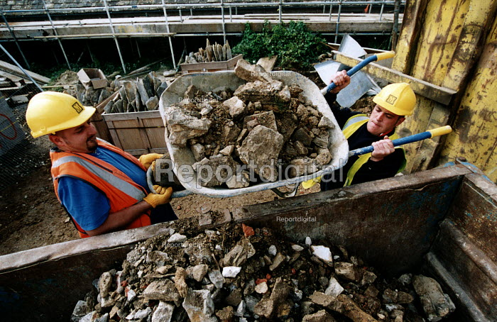 Construction workers removing rubble to a skip using a wheelbarrow. Restoration of Whatley Manor, Malmesbury. Midas construction site. - Paul Box - 2002-10-14