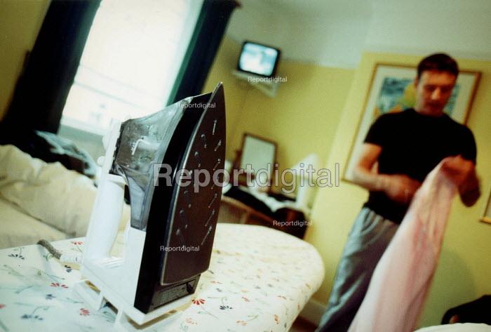 Man ironing shirts at home. - Paul Box - 2002-06-14