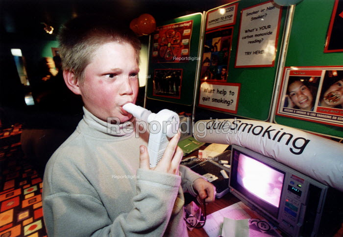 Young teenager measuring lung capacity on a quit smoking display, Weston Super Mare. Organised by Connexions. - Paul Box - 2002-03-14