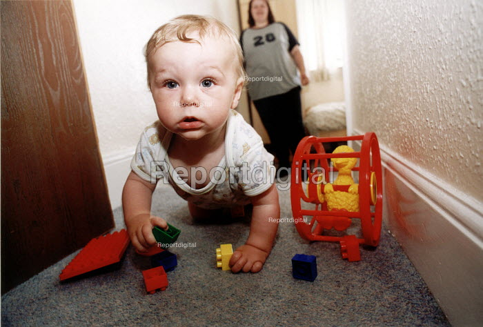 Mother and baby playing with toys in a refuge for battered women. Weston Super Mare. - Paul Box - 2001-10-01