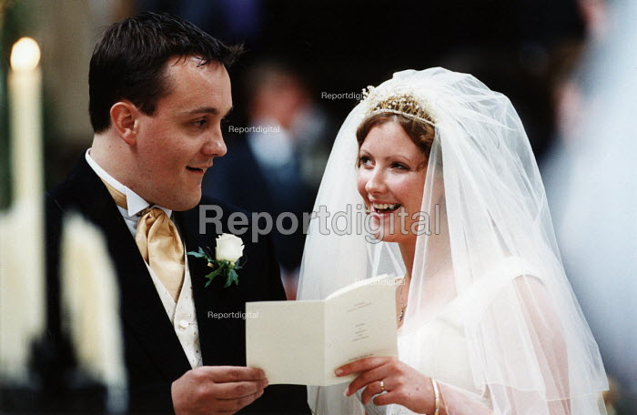 Bride and groom sing hymns during their wedding ceremony, Essex. - Paul Box - 2002-06-20