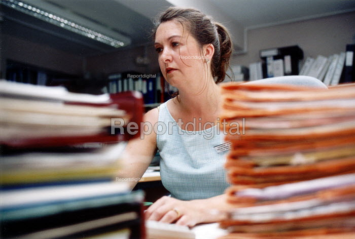 Medical secretary with folders of manual records, Velindre Hospital Cardiff, South Wales - Paul Box - 2001-07-14