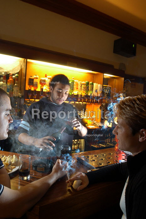 A worker in bar breathes in passive smoke from customers. - Paul Box - 2003-11-01