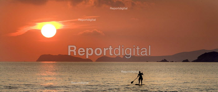 A stand up paddle surfer at Newgale beach in the sunset, Pembrokeshire. - Paul Box - 2008-09-27