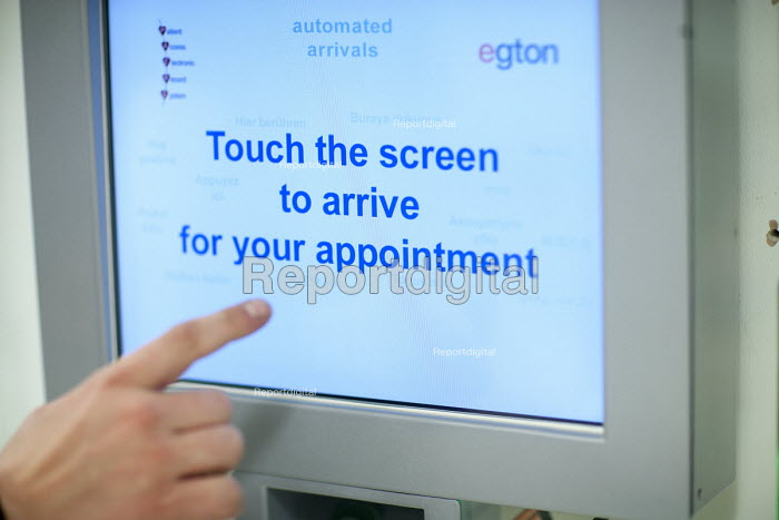 An automated arrivals kiosk interactive touch screen with various languages, NHS GP surgery and walk-in service, at Boots Broadmead Medical Centre, in Bristol. - Paul Box - 2009-09-02