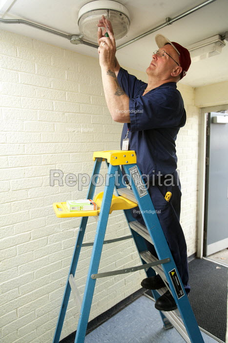 Selwood Housing maintenance man replacing a bulb from his step ladder. Selwood manage and maintain quality affordable housing and provide support services for people in housing need - Paul Box - 2009-08-03