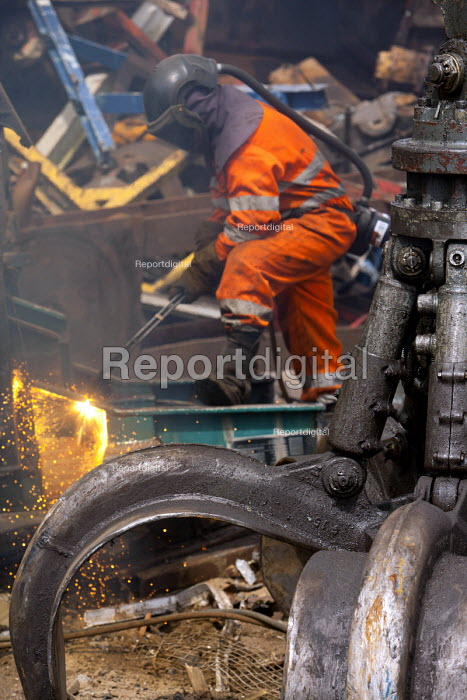 A man cuts metal plates with an oxyacetylene torch. SITA metal recycling facility at Boreham, Chelmsford. - Paul Box - 2010-04-26