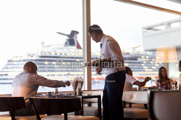 Wealthy people enjoying a drink whilst a cruise ship arrives into Monaco. - Paul Box - 2011-09-17