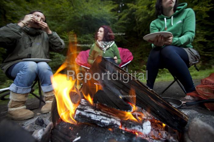 Women eating food around a campfire at Pool Farm Campsite, Porlock, Somerset. - Paul Box - 2011-08-09