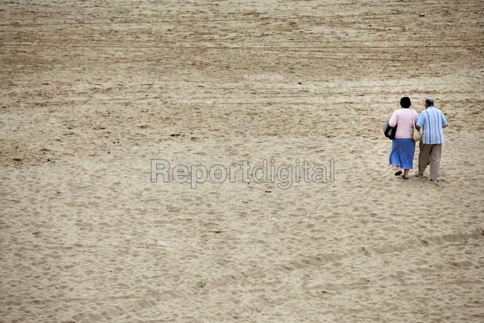 An elderly couple walking on Tenby Beach, Pembrokeshire, Wales. - Paul Box - 2009-09-26