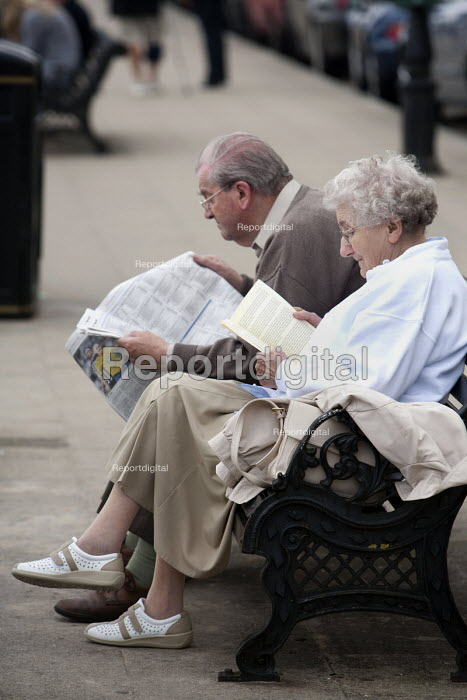 An elderly couple sitting on a bench reading, Tenby, Pembrokeshire, Wales. - Paul Box - 2009-09-26
