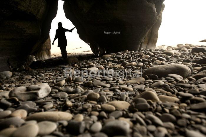 A woman walking through the caves at Marros Beach, Pembrokeshire, Wales. - Paul Box - 2009-10-04