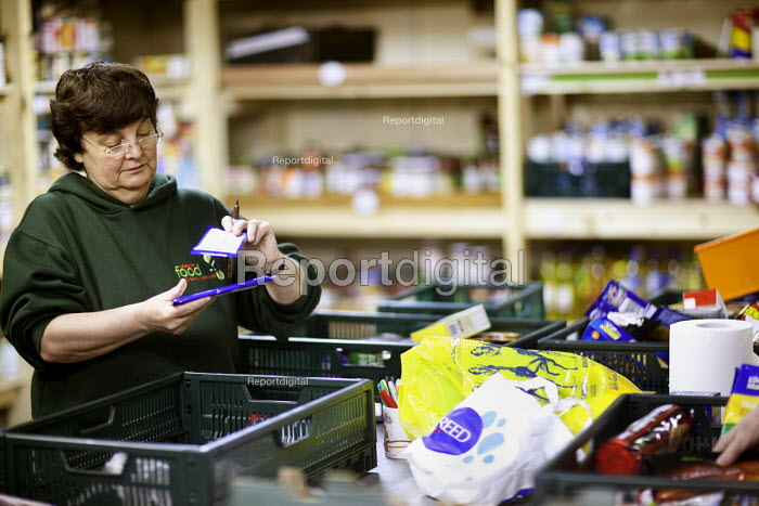 A volunteer in the warehouse sorts donated food at the Cardiff Foodbank a franchise of the Trussell Trust and a part of the National Foodbank Network. It is a project to help and support those suffering financial hardship and who are facing the reality of being unable to feed themselves or their families - Paul Box - 2012-05-10