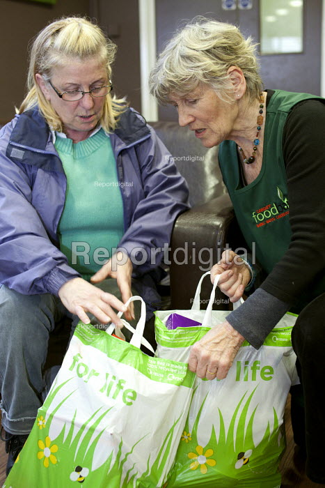 A volunteer gives some bags of food to a Foodbank user at the City Foodbank Centre. Cardiff Foodbank is part of the Trussell Trust and the National Foodbank Network. It is set up to help and support those suffering hardship. - Paul Box - 2012-05-10