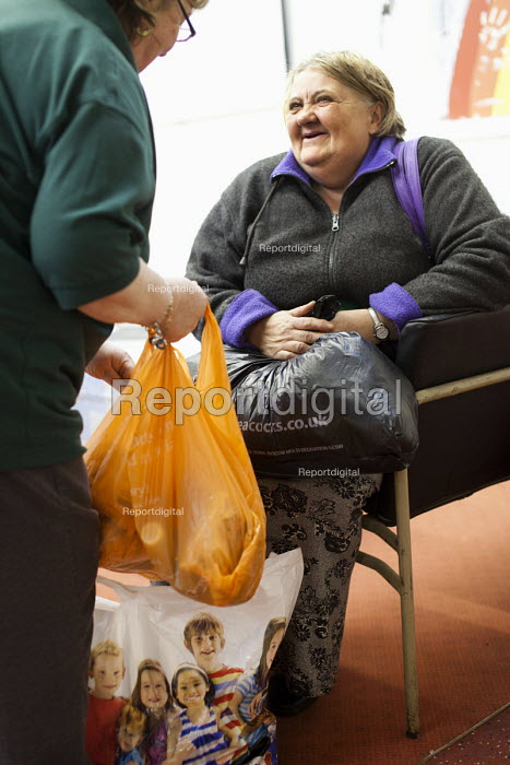 A volunteer gives some bags of food to a Foodbank user at the Ely Foodbank Centre. Cardiff Foodbank is part of the Trussell Trust and the National Foodbank Network. It is set up to help and support those suffering hardship. - Paul Box - 2012-05-10