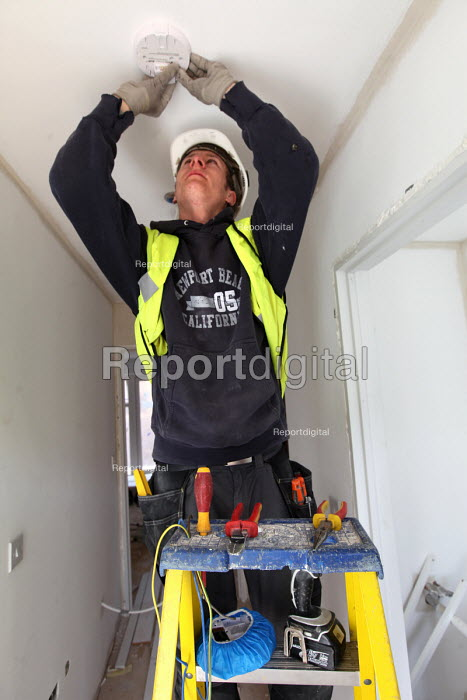 An electrician installing a smoke alarm in new housing near Taunton, Somerset. - Paul Box - 2012-03-22