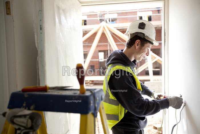 An electrician working on the mains supply, new housing near Taunton, Somerset. - Paul Box - 2012-03-22